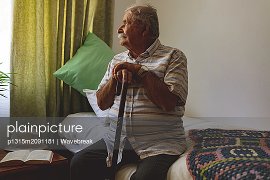 Senior man looking outside the window while sitting alone at nursing home - p1315m2091181 by Wavebreak
