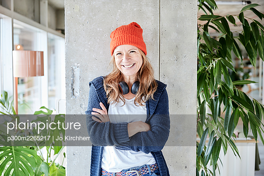 Smiling woman with arms crossed standing against column at home - p300m2265217 by Jo Kirchherr