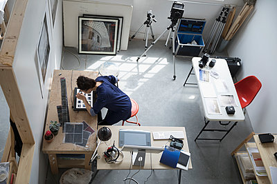 View from above female photographer reviewing photographic slides in art studio - p1192m1490266 by Hero Images