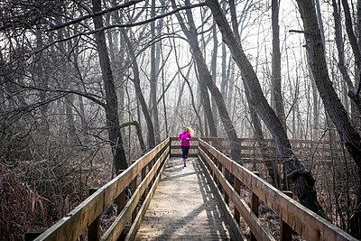Woman running on wooden bridge through forest - p300m1355944 by Simona Pillola
