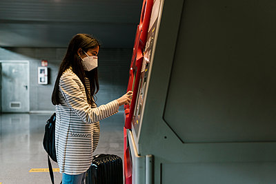 Woman with face mask using kiosk for buying train ticket during COVID-19 - p300m2240310 by Ezequiel Giménez