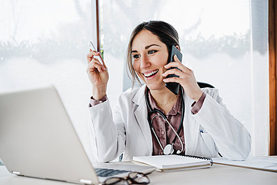 Smiling female doctor looking at laptop while talking on mobile phone in hospital - p300m2265695 by Eva Blanco