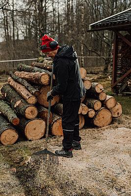Man raking wood chips - p312m2191249 by Jennifer Nilsson