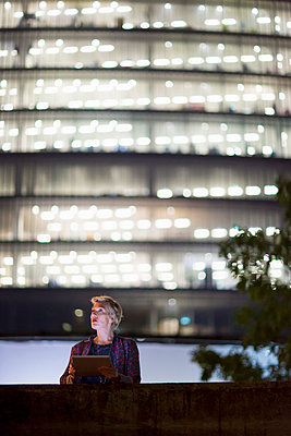 Mature businesswoman using digital tablet in front of office building at night, London, UK - p429m999712 by dotdotred
