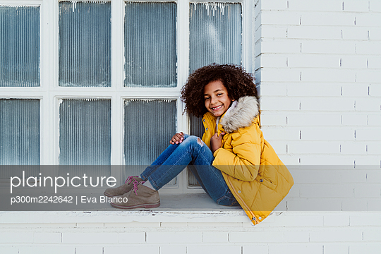 Portrait of smiling girl wearing yellow jacket sitting on window sill - p300m2242642 by Eva Blanco