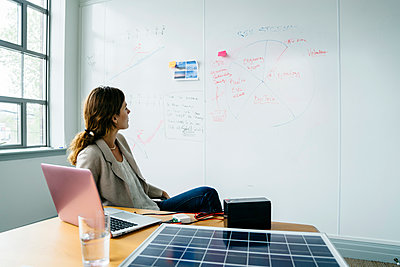 Businesswoman looking at diagram on whiteboard while working over solar panel in office - p1166m1474621 by Cavan Images