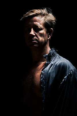 Dramatic portrait of a man on a black background - p1540m2195825 by Marie Tercafs