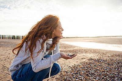 Redheaded woman collecting shell on the beach - p300m2023968 by Kniel Synnatzschke