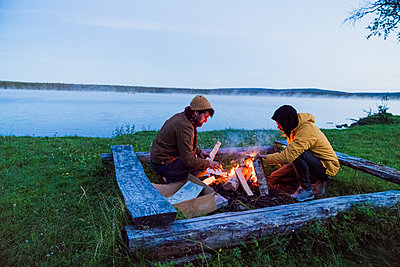 Sweden, Lapland, Two friends preparing a bonfire at the lakeshore - p300m2042292 by Kike Arnaiz