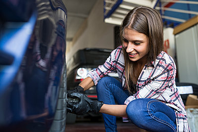 Young woman wearing gloves and screwing wheel of car working in repair shop - p300m2155100 by Andrés Benitez