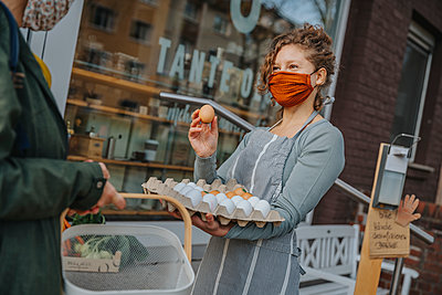 Store owner presenting eggs to customer at organic food store, Cologne, NRW, Germany - p300m2256179 von Mareen Fischinger