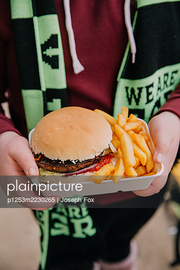 Soccer fan with Hamburger with Pommes - p1253m2230265 by Joseph Fox