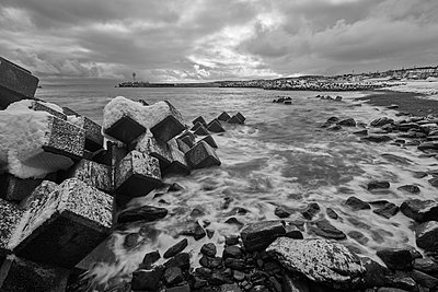 Snow-covered wave breakers on a rocky beach in winter. - p1100m1520073 by Mint Images