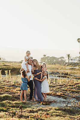 Lifestyle portrait of family with young girls smiling at beach sunset - p1166m2165887 by Cavan Images