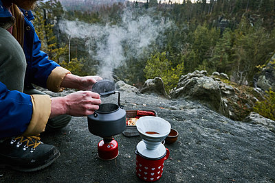 Man is making coffee with a gas cooker - p1573m2175266 by Christian Bendel