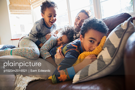 Portrait happy mother and children cuddling on living room sofa - p1023m2016521 by Sam Edwards