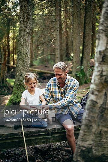 Smiling father helping daughter in cutting on footbridge in forest - p426m2213159 by Maskot