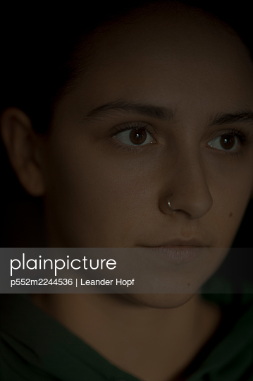 Portrait of young woman with nose piercing - p552m2244536 by Leander Hopf
