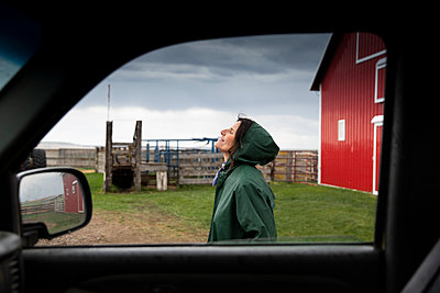 Serene female farmer standing outside truck on farm - p1192m2109741 by Hero Images