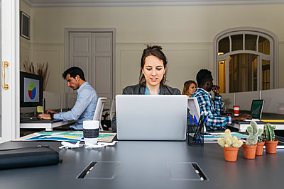 Young businesswoman using laptop, colleagues working in background - p300m1460330 by Josep Rovirosa