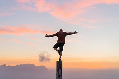 Spain, Barcelona, Natural Park of Sant Llorenc, man standing on pole at sunset - p300m2058577 by VITTA GALLERY