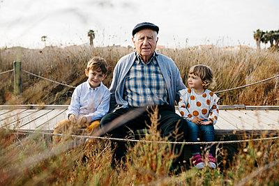 Portrait of grandfather sitting with his grandchildren side by side on boardwalk - p300m2103268 von Josep Rovirosa