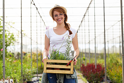Portrait of beautiful young woman holding wooden box with plants in the greenhouse - p300m2132055 by Josep Suria