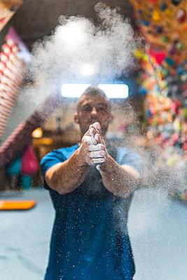 Young sportsman dusting talcum powder on hands in health club - p300m2275340 by Josu Acosta