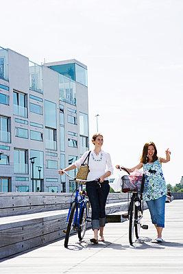 Two women riding bikes Skane Sweden. - p31221101f by Plattform