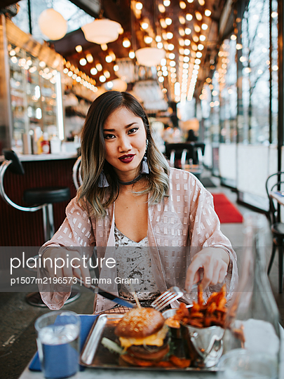 Asian woman sits in fast food restaurant - p1507m2196573 by Emma Grann