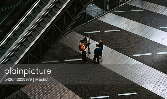 High angle view of male entrepreneurs discussing with female colleagues in meeting on walkway - p426m2238979 by Maskot
