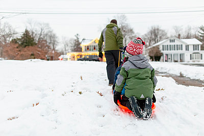 Rear view of father pulling children through the snow on  orange sled - p1166m2152059 by Cavan Images