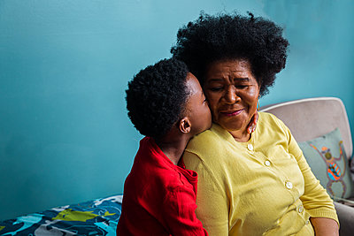 Grandson kissing grandmother on cheek by blue wall at home - p1166m2279368 by Cavan Images