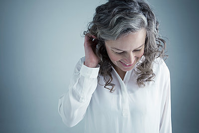 Portrait smiling Caucasian mature woman with hands in curly gray hair looking down - p1192m1213216 by Hero Images