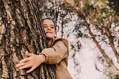 Smiling cute girl hugging tree while looking away at park - p300m2225497 by Eloisa Ramos