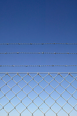 Barbed wire fence against blue sky - p388m701856 by L.B.Jeffries