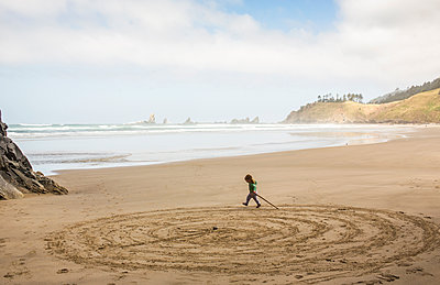 Caucasian girl drawing circles on beach with stick - p555m1303290 by Adam Hester
