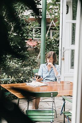Woman with e-book on terrace - p586m1178365 by Kniel Synnatzschke
