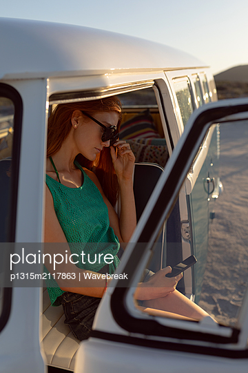 Beautiful woman with sunglasses using mobile phone on front seat of camper van at beach - p1315m2117863 by Wavebreak