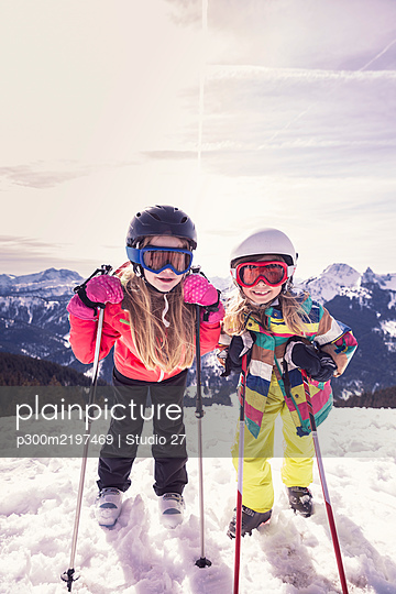 Excited sisters with skis standing on sw covered mountain in winter at Spitzingsee, Bavaria, Germany - p300m2197469 by Studio 27