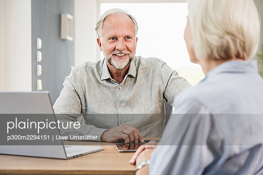 Smiling mature businessman discussing with female colleague at home office - p300m2294151 by Uwe Umstätter