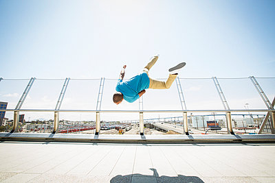 Young man somersaulting on a bridge.  - p1100m1038918 by Mint Images