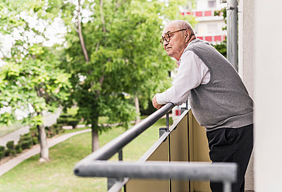 Senior man standing on balcony looking at distance - p300m2189173 by Uwe Umstätter