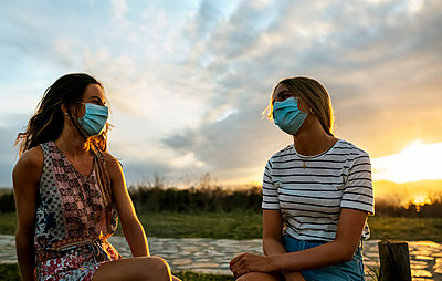 Women in protective face masks maintaining social distance while sitting against sky during sunset - p300m2221420 by Marco Govel