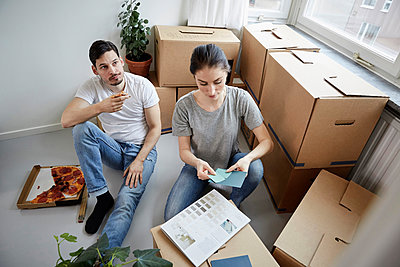 Thoughtful couple with pizza and color swatches during new home relocation - p426m2097840 by Maskot