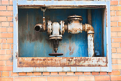 Rusting pipes inside red brick wall - p924m805829f by Ditto