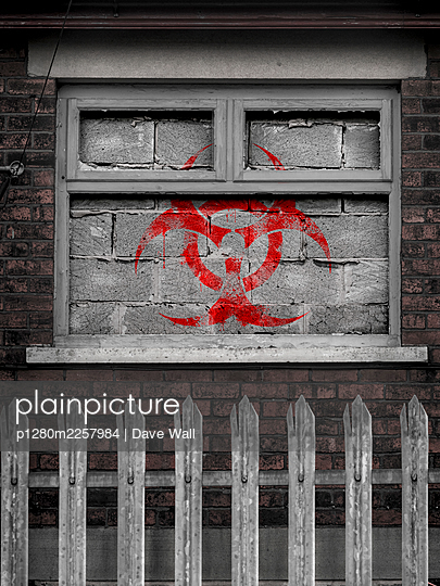 Red biohazard symbol painted on bricked up window - p1280m2257984 by Dave Wall
