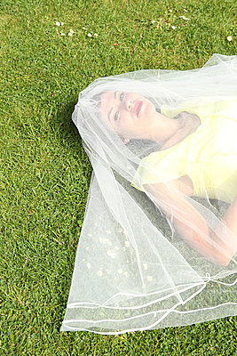 Bride lying on the lawn - p045m831254 by Jasmin Sander