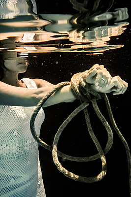 Woman Tied Up with Rope Drowning Under Water  - p1019m2107499 by Stephen Carroll