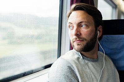 Mann hört im Zug Musik - p1114m1159733 von Carina Wendland